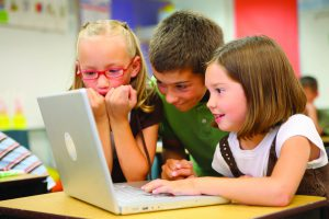 Three children look at a laptop together.