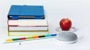 Image of school books, a tablet, apple, and smart speaker.
